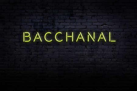 Neon sign on brick wall at night. Inscription bacchanal