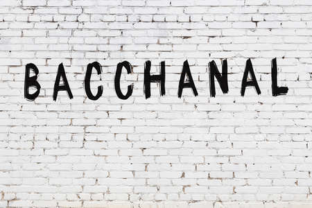 White brick wall with inscription bacchanal handwritten with black paint 写真素材