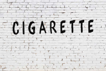 White brick wall with inscription cigarette handwritten with black paint Stok Fotoğraf