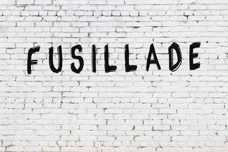 Inscription fusillade written with black paint on white brick wall. Stok Fotoğraf