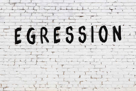 Inscription egression written with black paint on white brick wall. Foto de archivo