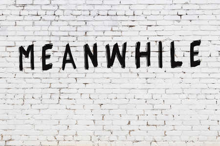 White brick wall with inscription meanwhile handwritten with black paint Standard-Bild