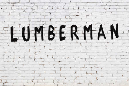 White brick wall with inscription lumberman handwritten with black paint