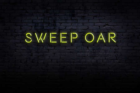 Neon sign on brick wall at night. Inscription sweep oar