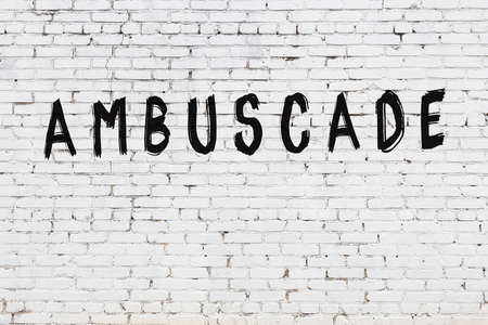 White brick wall with inscription ambuscade handwritten with black paint