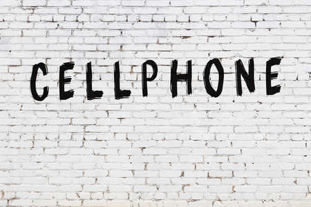 White brick wall with inscription cellphone handwritten with black paint