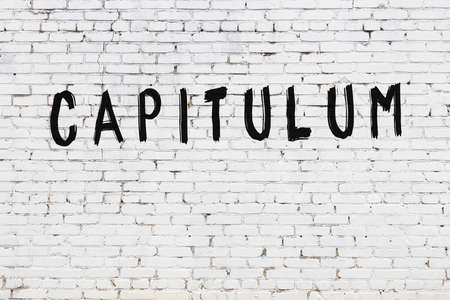 White brick wall with inscription capitulum handwritten with black paint