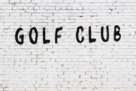 Inscription golf club written with black paint on white brick wall.