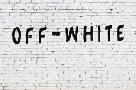 Inscription off-white written with black paint on white brick wall.