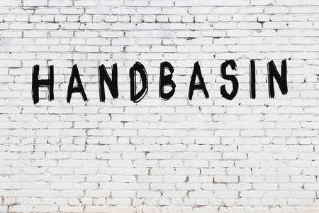 White brick wall with inscription handbasin handwritten with black paint Standard-Bild