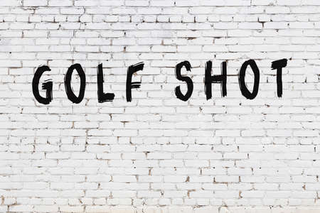 White brick wall with inscription golf shot handwritten with black paint