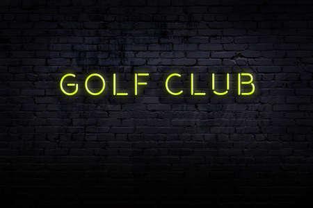 Neon sign with inscription golf club against brick wall. Night view Standard-Bild