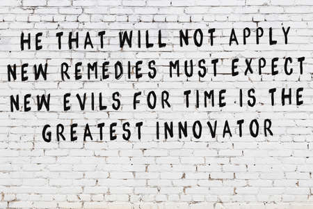 White brick wall and  black painted inscription of  wise quotation