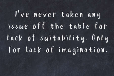 Smart saying handwritten with chalk on black desk