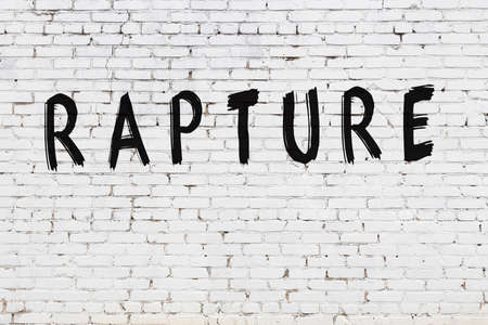White brick wall with inscription rapture handwritten with black paint
