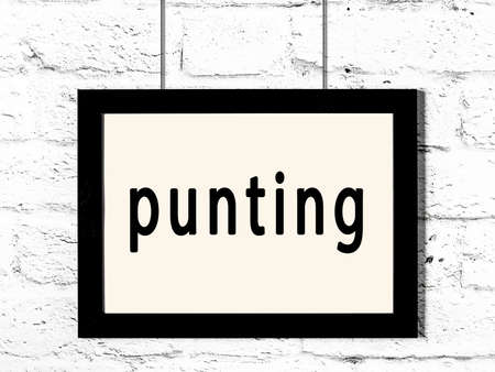 Black wooden frame with inscription punting hanging on white brick wall