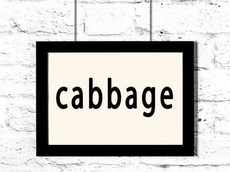 Black wooden frame with inscription cabbage hanging on white brick wall