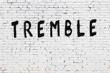 Inscription tremble written with black paint on white brick wall. 版權商用圖片