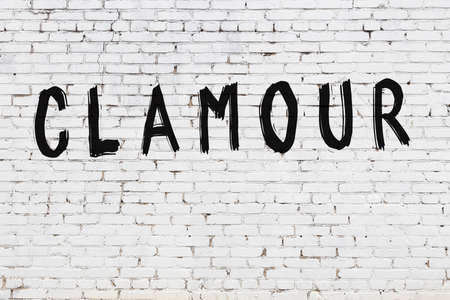 Inscription clamour written with black paint on white brick wall.