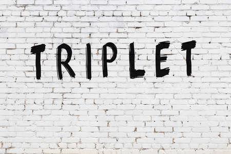 Inscription triplet written with black paint on white brick wall. Stockfoto