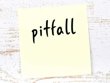 Concept of reminder about pitfall. Yellow sticky sheet of paper on wooden wall with inscription
