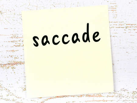 Concept of reminder about saccade. Yellow sticky sheet of paper on wooden wall with inscription Stock Photo