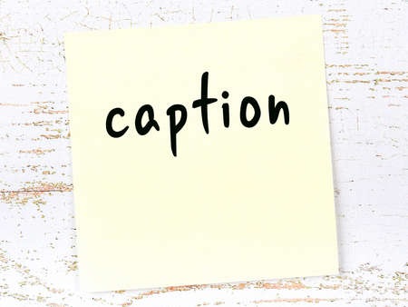 Concept of reminder about caption. Yellow sticky sheet of paper on wooden wall with inscription