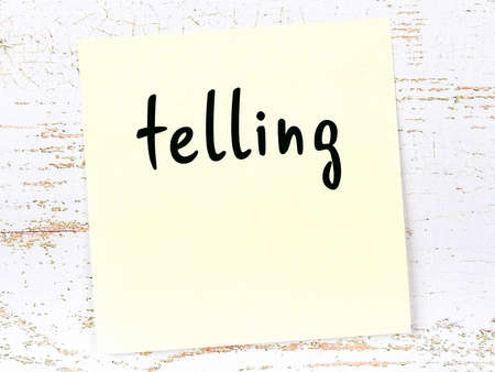 Concept of reminder about telling. Yellow sticky sheet of paper on wooden wall with inscription