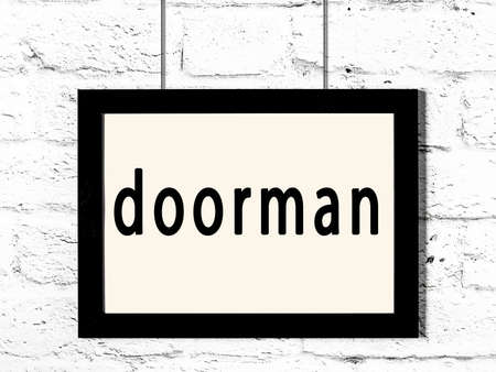 Black wooden frame with inscription doorman hanging on white brick wall