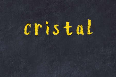 Chalk handwritten inscription cristal on black desk