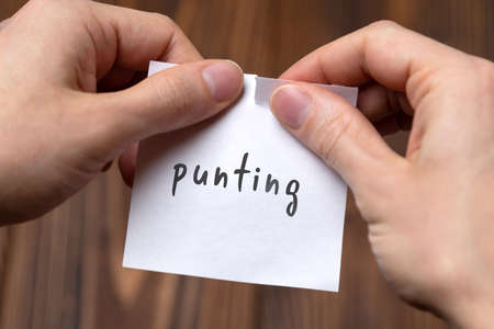 Cancelling punting. Hands tearing of a paper with handwritten inscription.