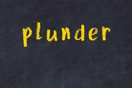 Chalk handwritten inscription plunder on black desk