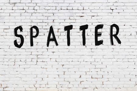 Inscription spatter written with black paint on white brick wall. Stok Fotoğraf