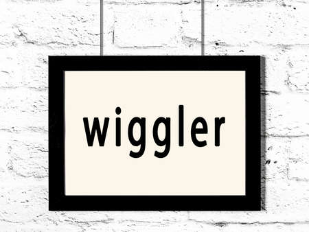 Black wooden frame with inscription wiggler hanging on white brick wall