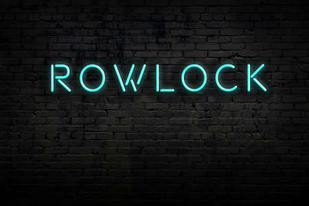 Neon sign with inscription rowlock against brick wall. Night view 版權商用圖片