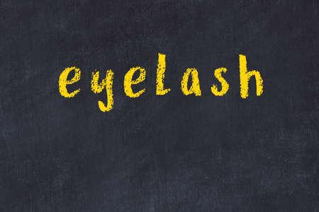 Chalk handwritten inscription eyelash on black desk