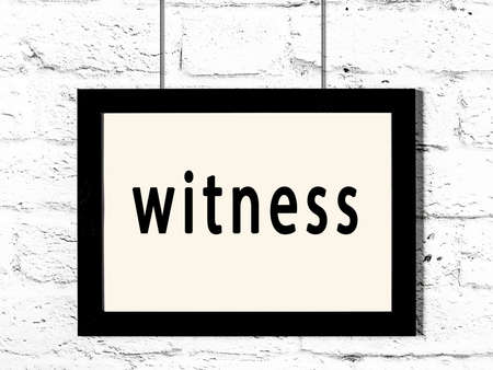 Black wooden frame with inscription witness hanging on white brick wall