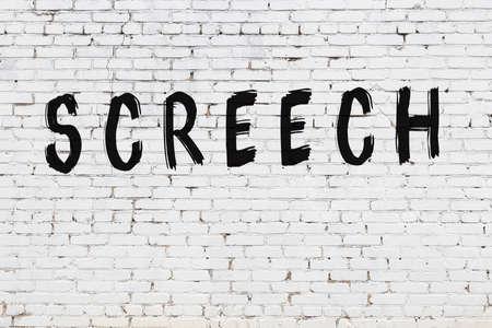 Inscription screech written with black paint on white brick wall.