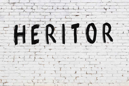 White brick wall with inscription heritor handwritten with black paint Banco de Imagens