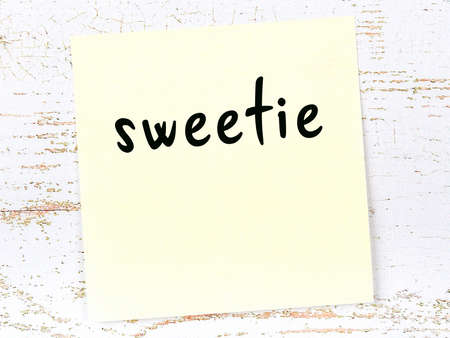 Concept of reminder about sweetie. Yellow sticky sheet of paper on wooden wall with inscription