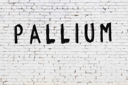White brick wall with inscription pallium handwritten with black paint
