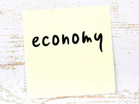 Yellow sticky note on wooden wall with handwritten inscription economy 版權商用圖片
