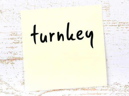 Yellow sticky note on wooden wall with handwritten inscription turnkey