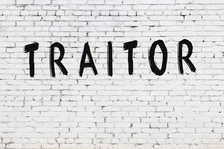 White brick wall with inscription traitor handwritten with black paint Stock Photo