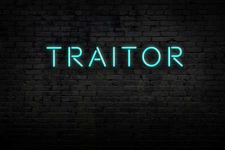Neon sign on brick wall at night. Inscription traitor