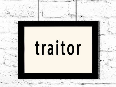 Black wooden frame with inscription traitor hanging on white brick wall Stock Photo