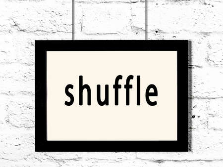 Black wooden frame with inscription shuffle hanging on white brick wall