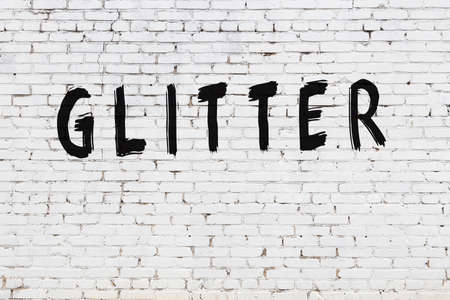 White brick wall with inscription glitter handwritten with black paint