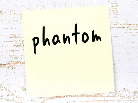 Concept of reminder about phantom. Yellow sticky sheet of paper on wooden wall with inscription