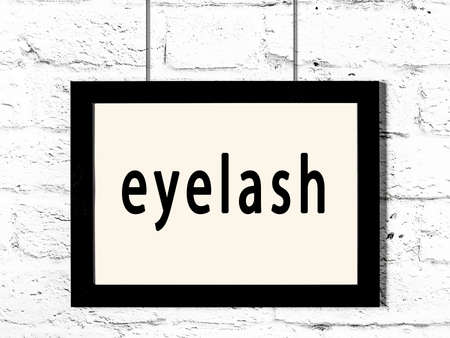 Black wooden frame with inscription eyelash hanging on white brick wall